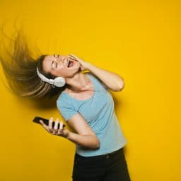 woman whipping her hair in the air while listening to music through headphones