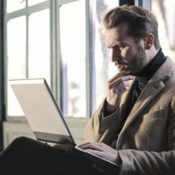 Man sitting and using laptop.
